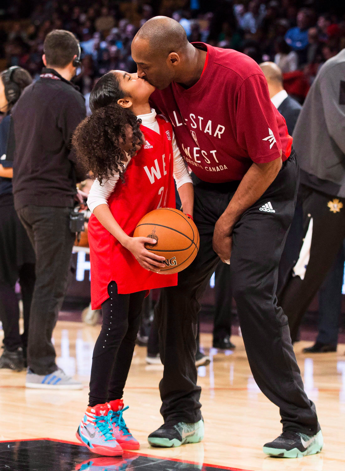 FATHER AND DAUGHTER — In this Feb. 14, 2016, file photo, Los Angeles Lakers Kobe Bryant (24) kisses his daughter Gianna on the court in warm-ups before the NBA All-Star Game in Toronto. Bryant and fellow NBA greats Tim Duncan and Kevin Garnett headlined a nine-person group announced Saturday as this year's class of enshrinees into the Naismith Memorial Basketball Hall of Fame.