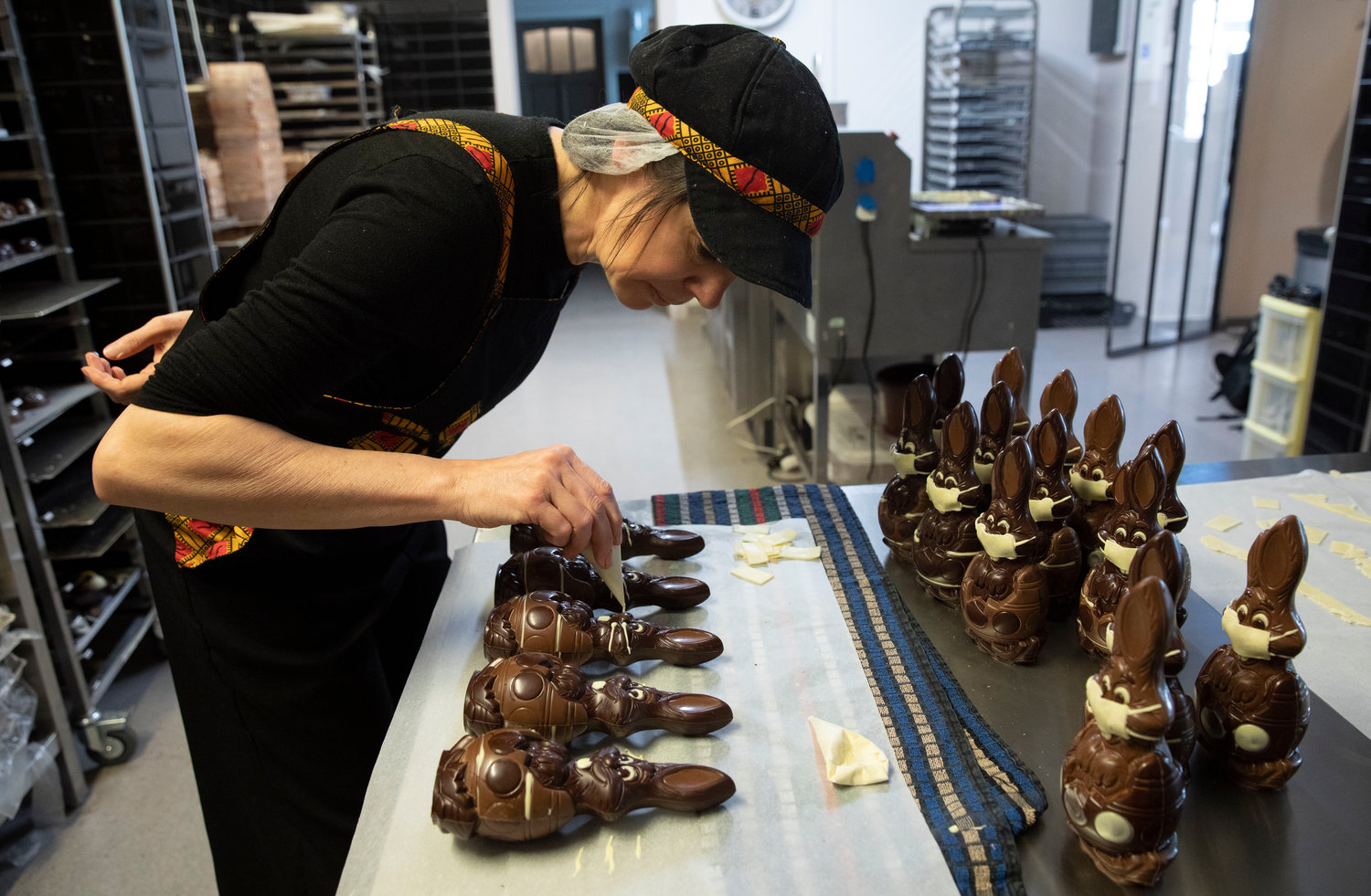 DECORATING — Genevieve Trepant decorates chocolate rabbits at her shop, Cocoatree, in Lonzee, Belgium.