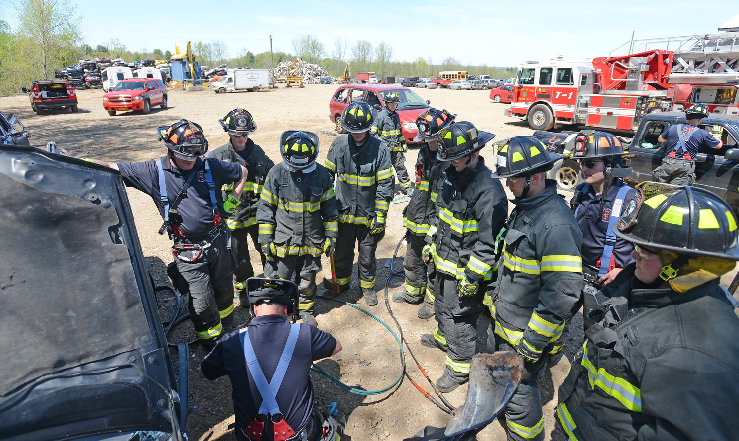 CLASS IN SESSION — New Rome Fire Department recruits watch as Firefighter Adam Palinski cuts into a car with hydraulic tools at Rubicon Recycling Thursday afternoon. Department officials said they have started training their new recruits in-house because the pandemic has temporarily closed the regular fire academy in Utica.