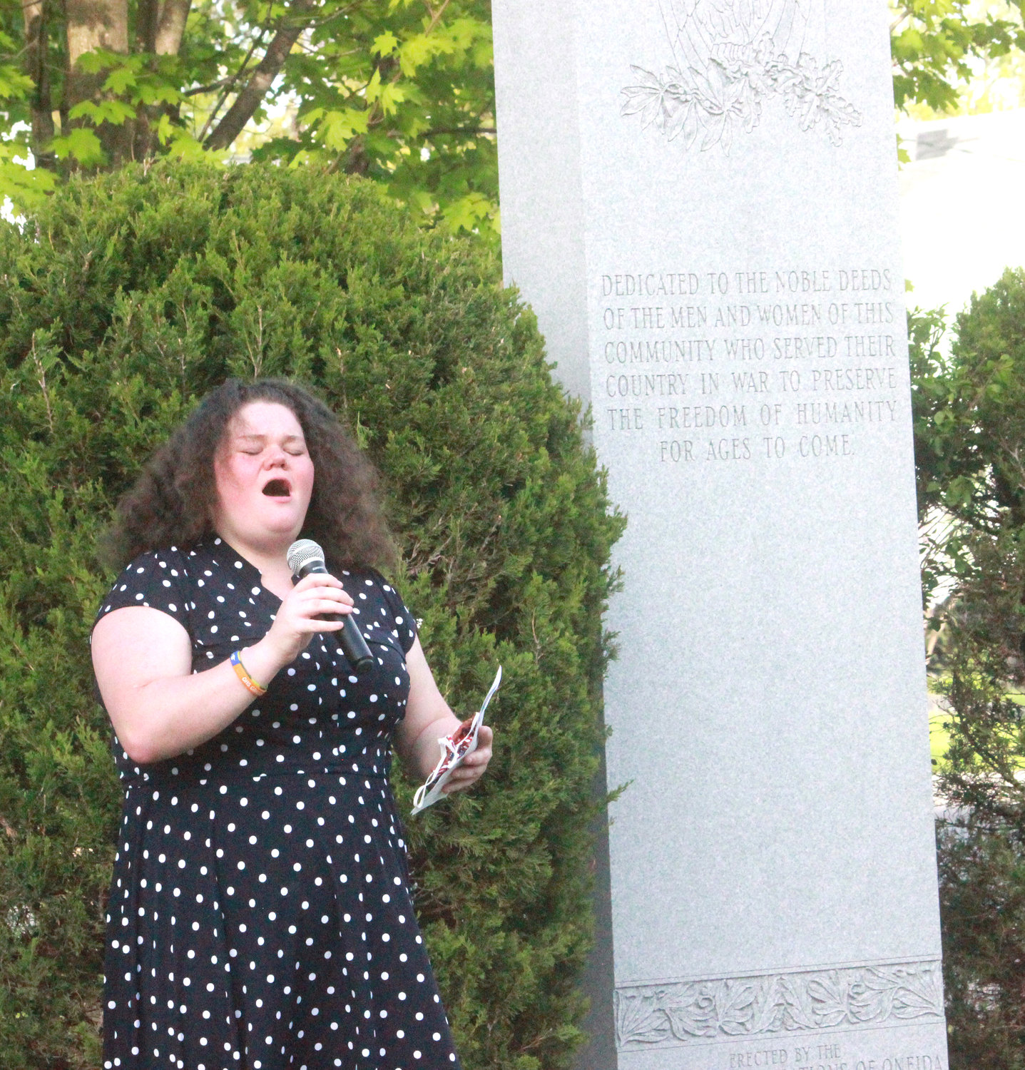 High School Senior Sage Carolla sings the national anthem at the Oneida Memorial Association Memorial Day observance event at Triangle Park on Friday.