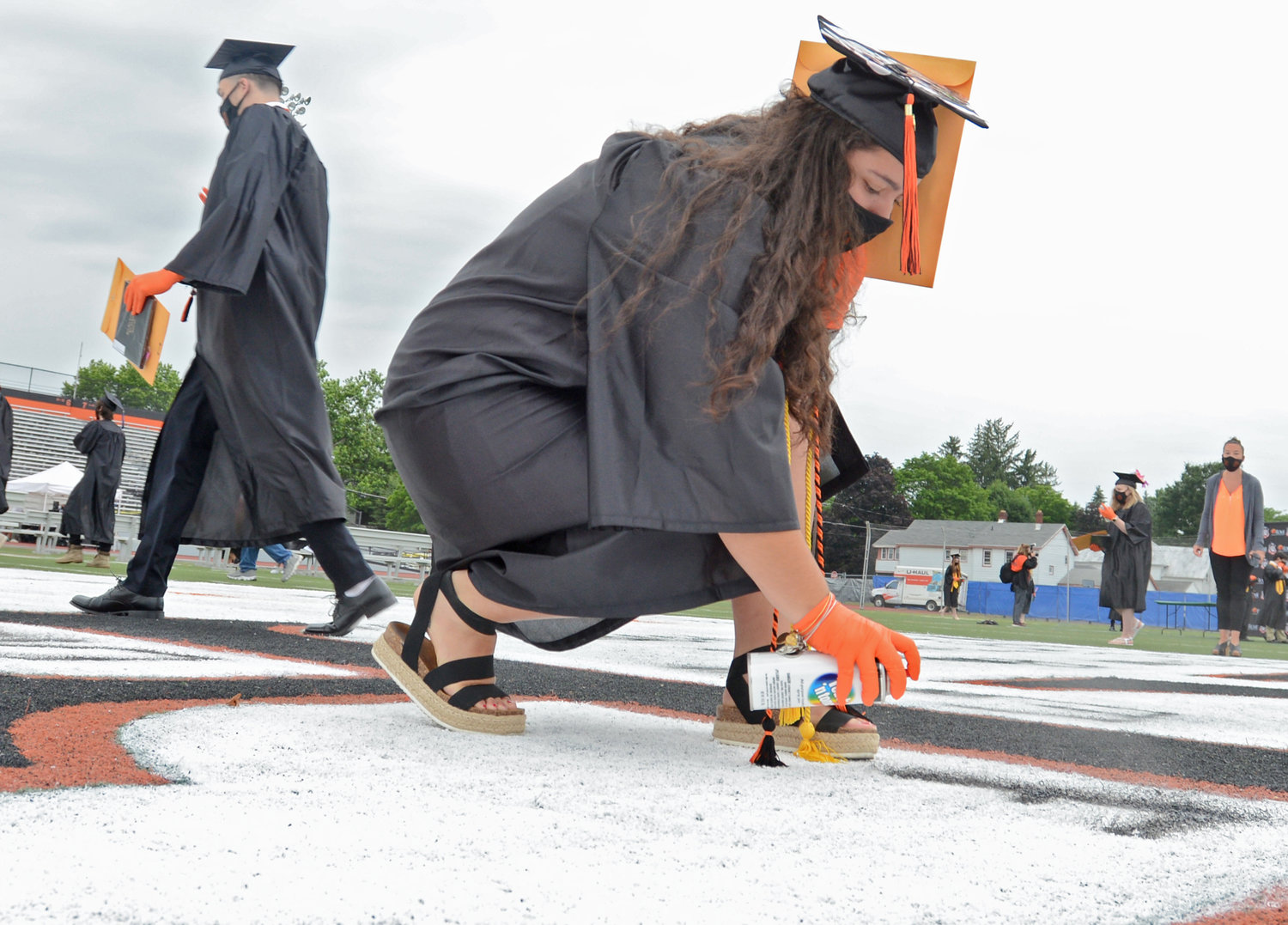 LEAVING HER MARK — Elana Calicchia spray paints her name into the turf at RFA after getting her diploma on Saturday.