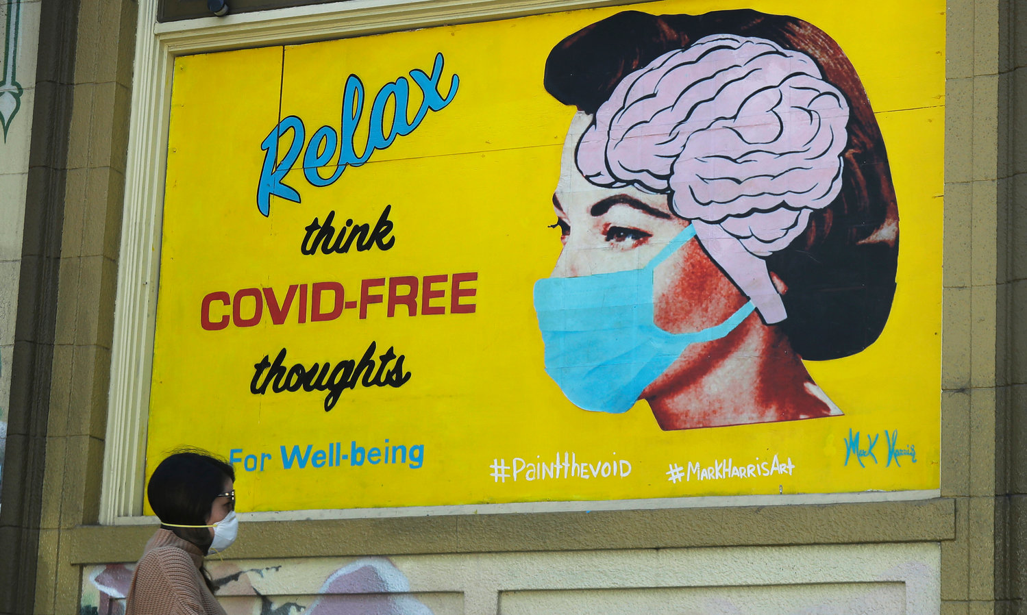 "THINK POSITIVE — A woman wears a face mask while walking under a sign that reads ""Relax think COVID free thoughts"" during the coronavirus outbreak in San Francisco. California health officials have reported the state's first coronavirus death of a child. (AP Photo)"