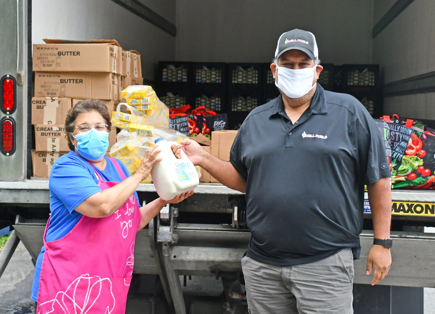 NOW THEY'VE GOT MILK — Buell Fuels Marketing Representative, Javier Lopez, right,  hands a gallon of milk to Country Pantry lead organizer Mary Zimbler at a food distribution event earlier this month. Another 299 gallons of milk, also donated to the Clark Mills pantry, is ready to be distributed to local families in need on the refrigerated truck behind them. This is the second such donation Buell Fuels has made to the The Country Pantry since May in an effort to aid both the hungry in the Clinton-Clark Mills-Westmoreland area and local dairy farmers who have been impacted by the ongoing COVID-19 pandemic.