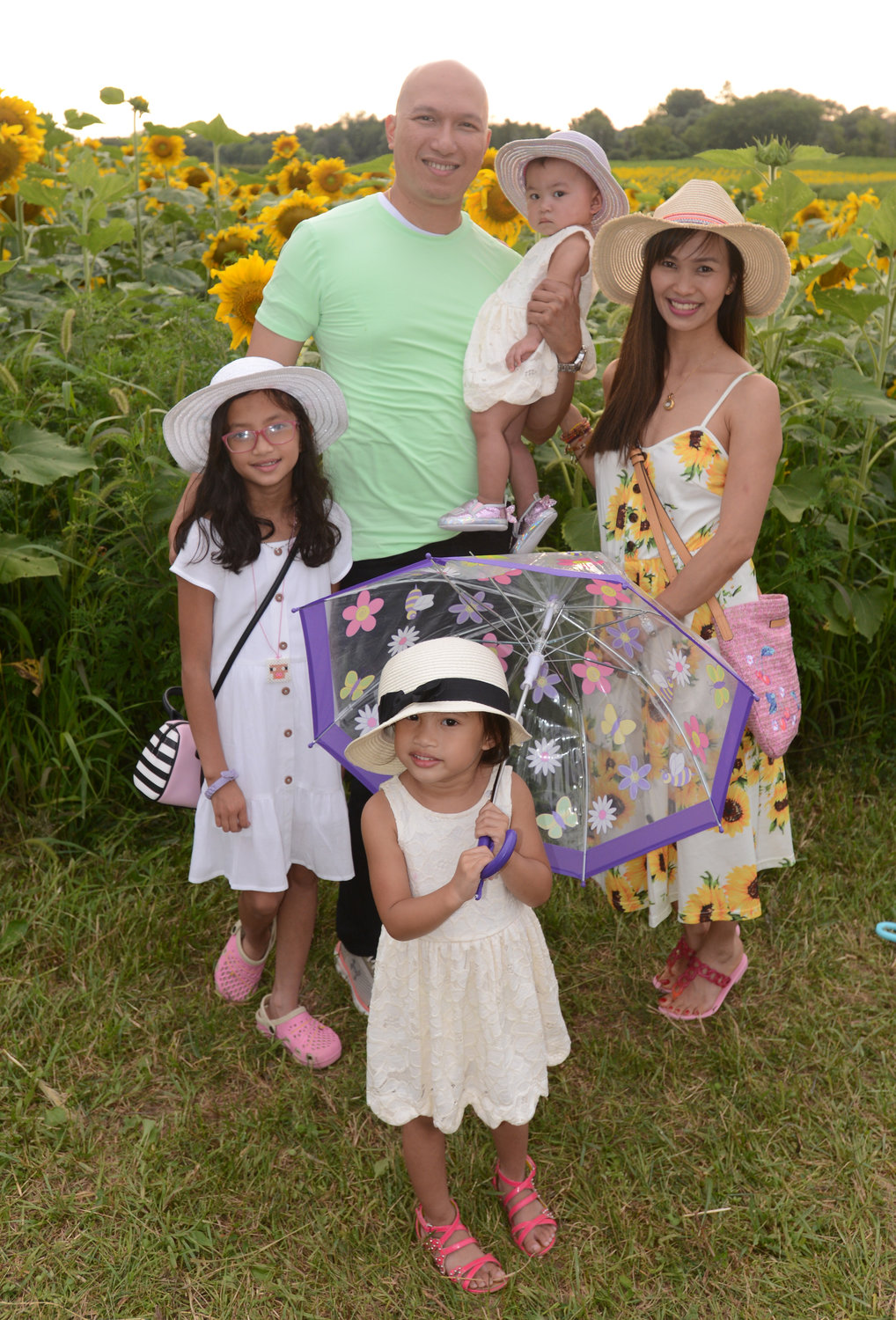 CAPTURING THE MOMENT — The Cruz family, who came all the way from Albany to enjoy the Wagner Farms sunflower fields, pose for a photo before taking their own selfies amid the late summer blooms. The family includes: Terence Cruz, holding Adeline Rose, 1; Evean Cruz, 9; mom Nelia Cruz; and Celyna Cruz, 3, with a cheerful umbrella.
