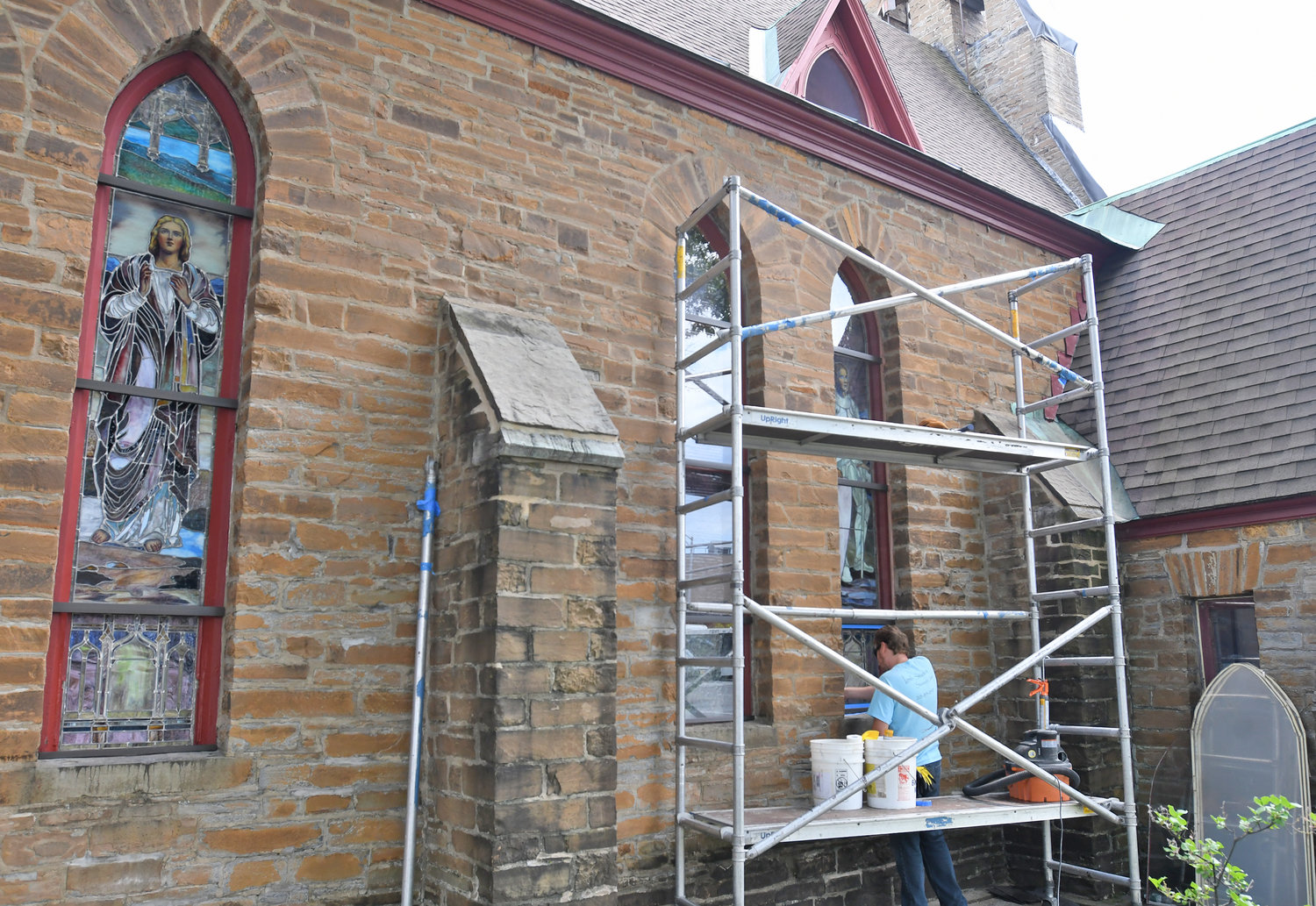 WORK IN PROGRESS — Michael McDonough, with J&R Lamb Studios, seals a stained glass window at the Zion Episcopal Church on Liberty Street Tuesday. Artists will be hard at work over the next couple days restoring the church's historic stained glass.