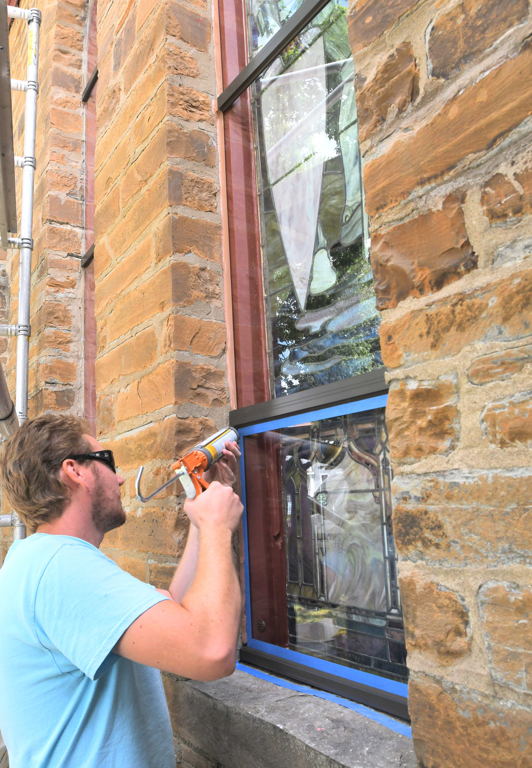 RESTORATION UNDERWAY — Michael McDonough, an artist with J&R Lamb Studios, Inc., in New Jersey, caulks a west window at Zion Episcopal Church on Liberty Street Tuesday afternoon.  Last year, the church received a $10,000 grant from Rome Community Foundation to help restore and refurbish the windows.