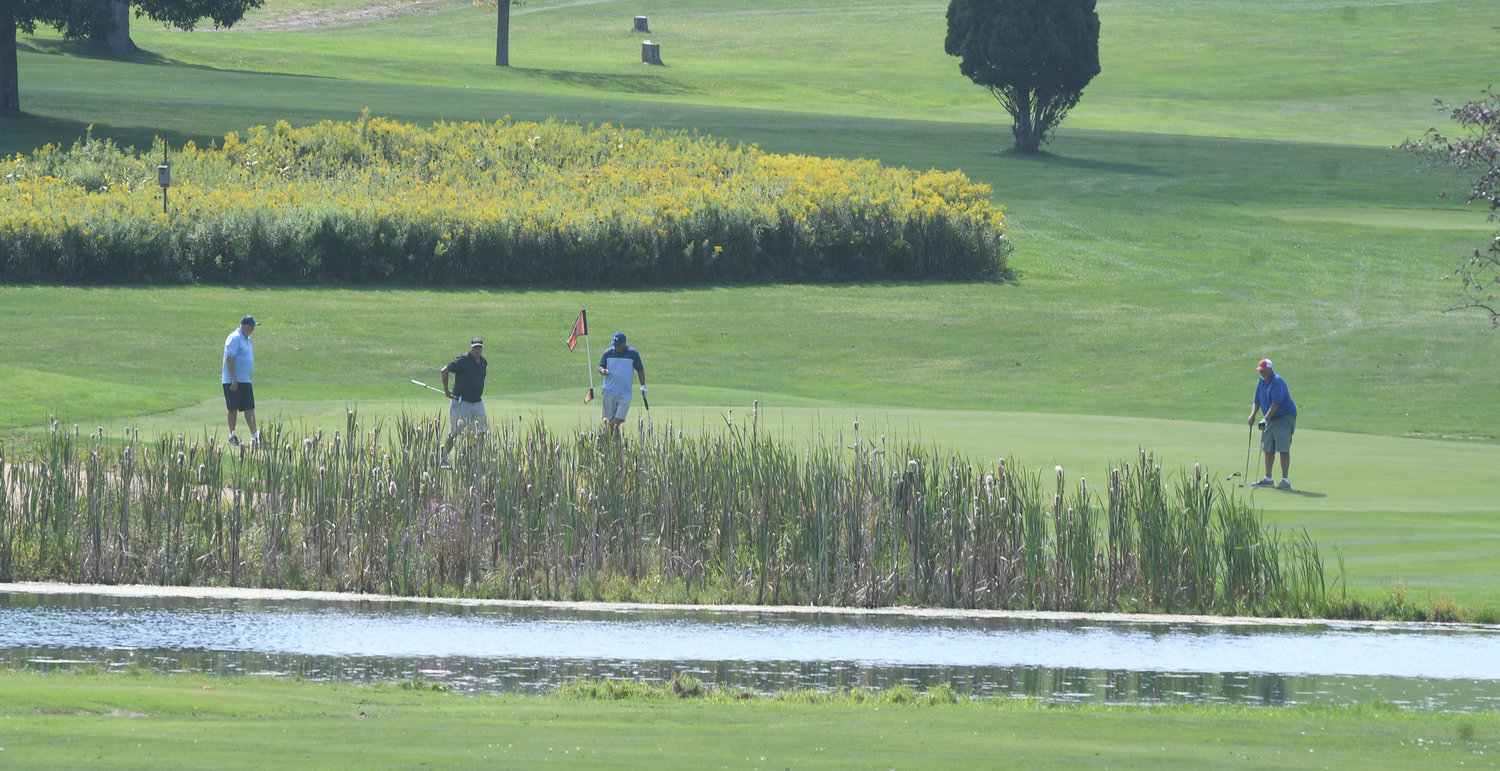 ON THE GREEN — Golfers putt on the 15th hole at The Skenandoa Club on Wednesday morning.