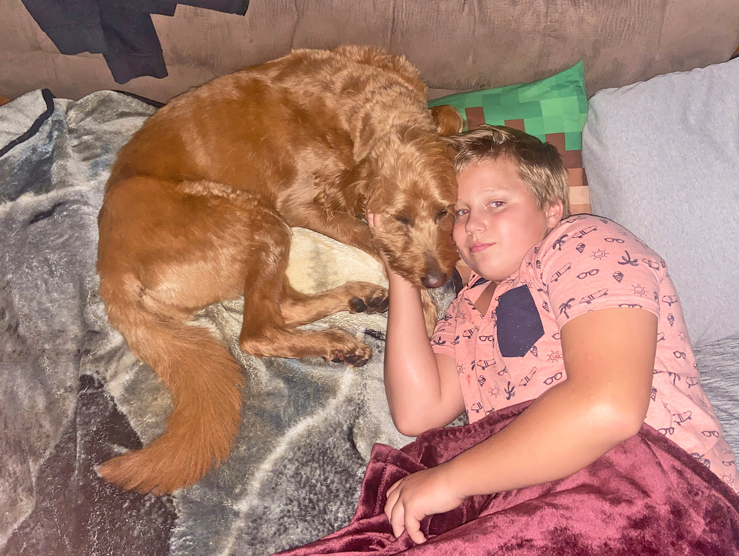 NEEDED REST — The Waterman family has been reunited with their four-year-old labradoodle Tia. 13-year-old William Waterman lays down with his canine companion, happy to have her back.