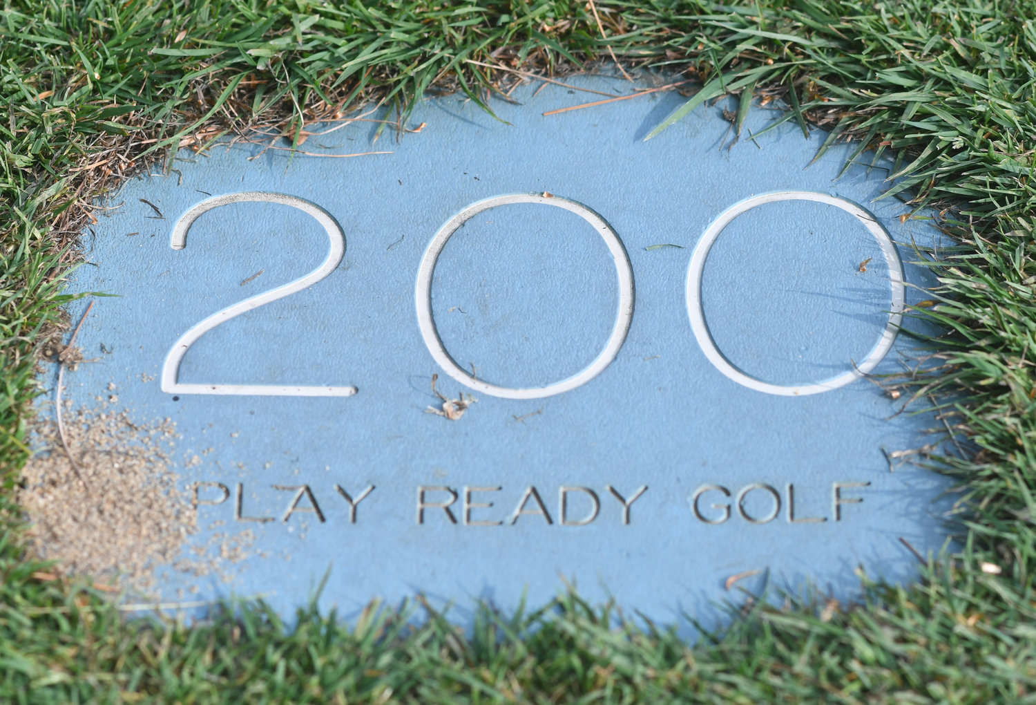 "YARDS TO GO — A yardage marker sits in the fairway at Thendara Golf Club on Thursday afternoon. It also holds a message to remind players to play ""ready golf"" to quicken the pace of play."