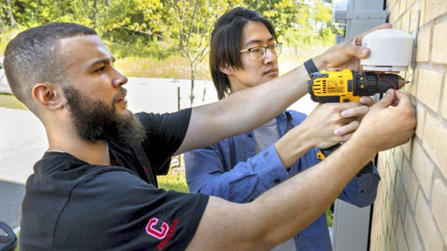 INSTALLING INTERNET OF THINGS — Doctoral candidate Alfredo Rodriguez, foreground, and Qingxuan Sun, a visiting Ph.D., install an Internet of Things-based outdoor air quality monitor in summer 2019 at Cornell University.