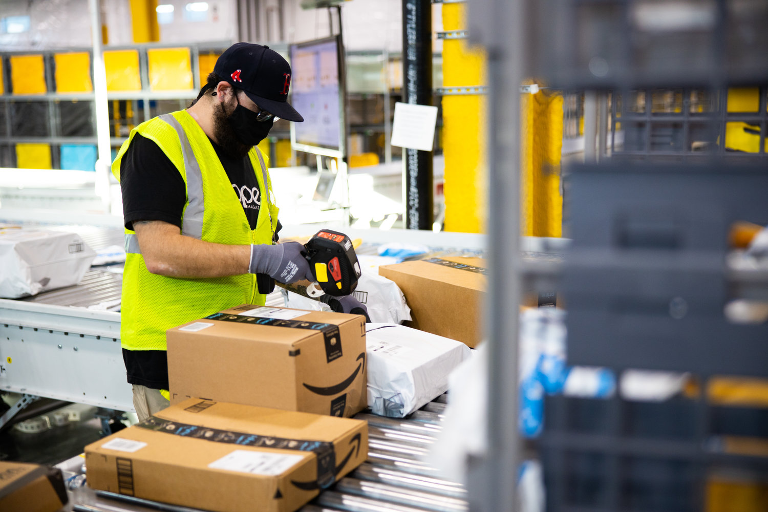 ON ITS WAY — An Amazon worker sorts a package in this company file photo. Amazon has announced a new delivery station currently under construction in East Syracuse will open for service early next year.
