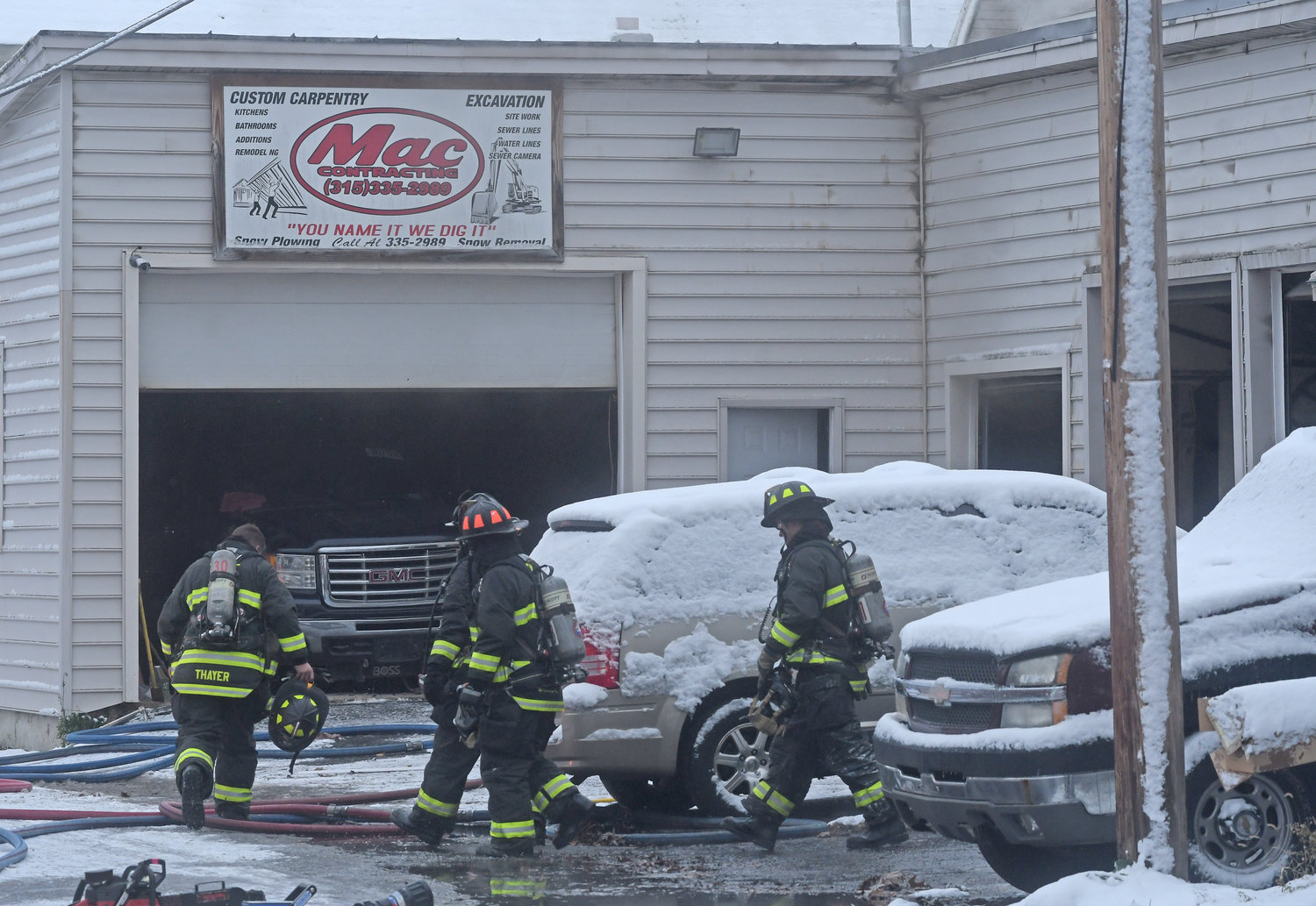 DAMAGED CONTAINED — Firefighters make their way into Mac Contracting at 402 Scott Ave. this morning. Fire officials said the fire damage was contained to two bays at the repair shop, with smoke damage throughout the building.
