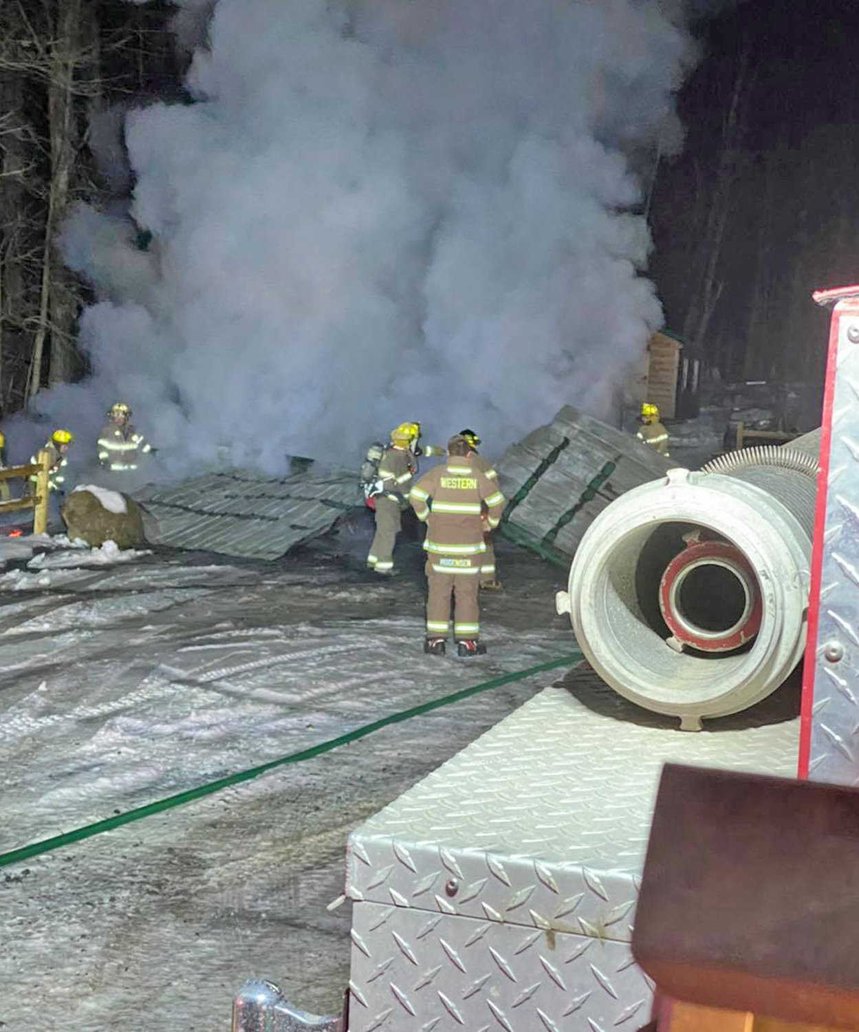 GARAGE FIRE — Western firefighters douse a collapsed garage fire on Carmichael Hill Road in the Town of Steuben Monday night.