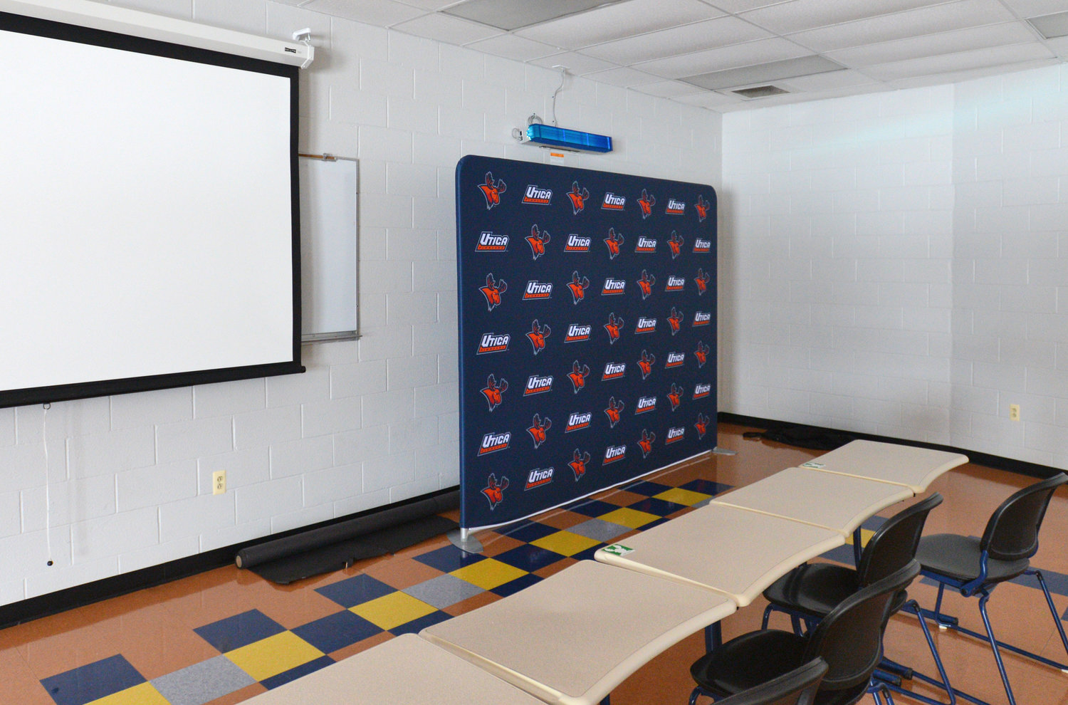 SPECIAL WALL LIGHTING — Shown here at upper right in an athletic facility classroom at Utica College is an AeroMed Germocidal Ultraviolet Fixture light, designed to irradiate air that may be contaminated with virus particles including COVID-19 and the flu. The college purchased 248 of the lights, and they were installed in every classroom and in the Gary Kunath Fitness Center.