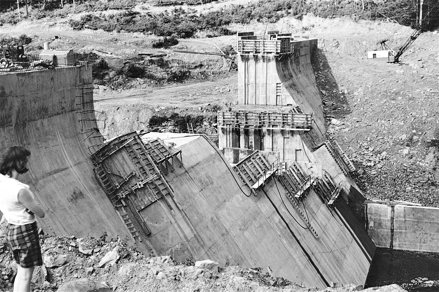 OVERLOOK — An unidentified person looks over the construction of Boyd Dam, in this photo from July 1959.The dam impounds water from Lake Tagasoke, to Fish Creek, where it is impounded by Kessinger Dam, and then flows to a mile-long rock tunnel to the reservoirs in Lee.