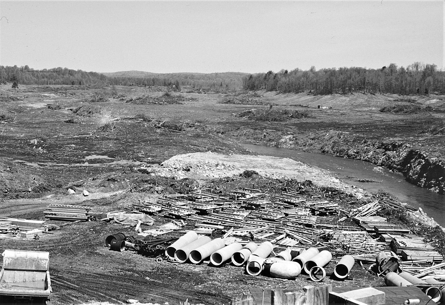 PIPING IT IN — Pipes lay in the foreground, as construction begins on the Boyd Dam in this photo, taken in May 1958. In the background is part of the 400-acre Lake Tagasoke.
