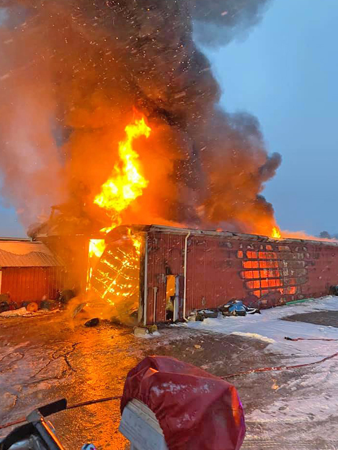 CHADWICKS BARN FIRE — Bright orange flames burst out of a barn at Collins Knoll Farm on Elm Street in Chadwicks Friday morning. Multiple fire departments spent several hours battling the blaze Friday morning.