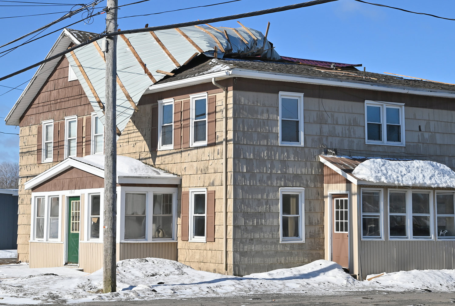 HIGH WINDS RIP ROOF — A sheet of metal roofing hangs off the top of 6866 S. James St. Tuesday, following Monday's heavy winds. Fire officials said no one was injured. They added that a second piece of metal roofing was blown into the roadway.