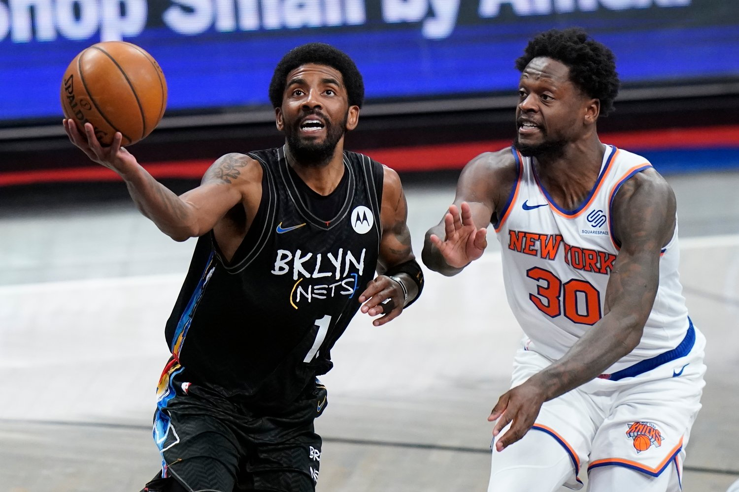DRIVING PAST — Nets guard Kyrie Irving drives past Knicks forward Julius Randle during the first half of an NBA game on Monday night in New York. Irving scored 40 points as the Nets won 114-12.