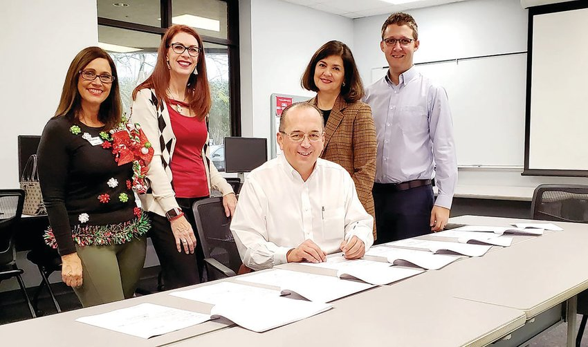 Bautech USA CEO Sergio Prahl signs the lease agreements for a planned facility at the Okeechobee Airport Industrial Park with members of the Okeechobee County Economic Development Corporation.