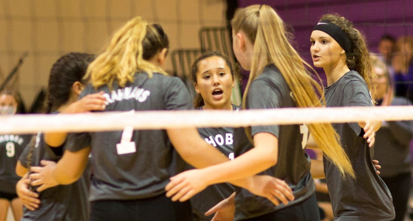 The Okeechobee Lady Brahman volleyball team huddles after scoring a point.
