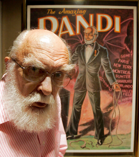 CORRECTS DAY OF DEATH TO TUESDAY, OCT. 20 INSTEAD OF MONDAY, OCT. 19 - FILE - In this Friday, June 29, 2007, file photo, James Randi is shown in front of a poster at his home in Fort Lauderdale, Fla. The Florida-based James Randi Educational Foundation announced its founder died Tuesday, Oct. 20, 2020, at 92. (AP Photo/Alan Diaz, File)
