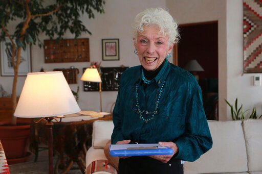 Get-out-the-vote letter writer Nancy Gehman poses for a photo at her home on Tuesday, Oct. 27, 2020, in Santa Fe, New Mexico. Gehman is one of 182,000 people who have participated in Vote Forward, a 50-state letter-writing campaign to more than 17.5 million homes. In the best of times, it's a massive logistical challenge to get millions out to vote. In 2020, the difficulty has been dramatically compounded: by fear of the coronavirus, by complications and confusion over mail-in ballots, by palpable anxiety over the bitter divisions in the country. (AP Photo/Cedar Attanasio)