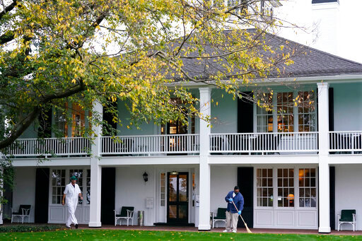 A worker sweeps leaves in front of the Augusta National Club house during a practice round for the Masters golf tournament Tuesday, Nov. 10, 2020, in Augusta, Ga. (AP Photo/David J. Phillip)