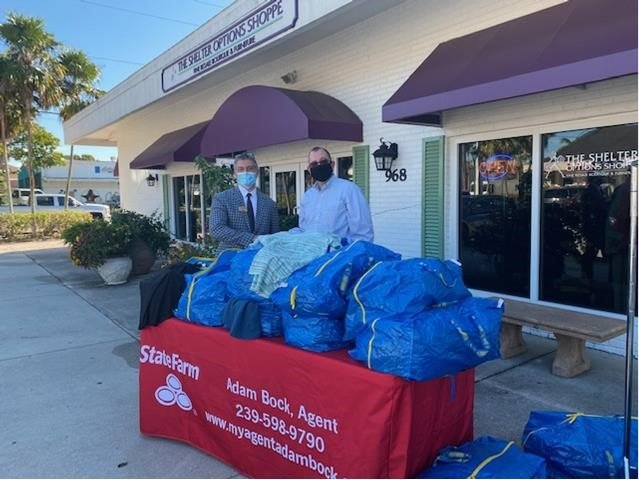 The Shelter Options Shoppe Manager Paul Kallenberg, left, and State Farm agent Adam Bock with donations of clothing for Options.