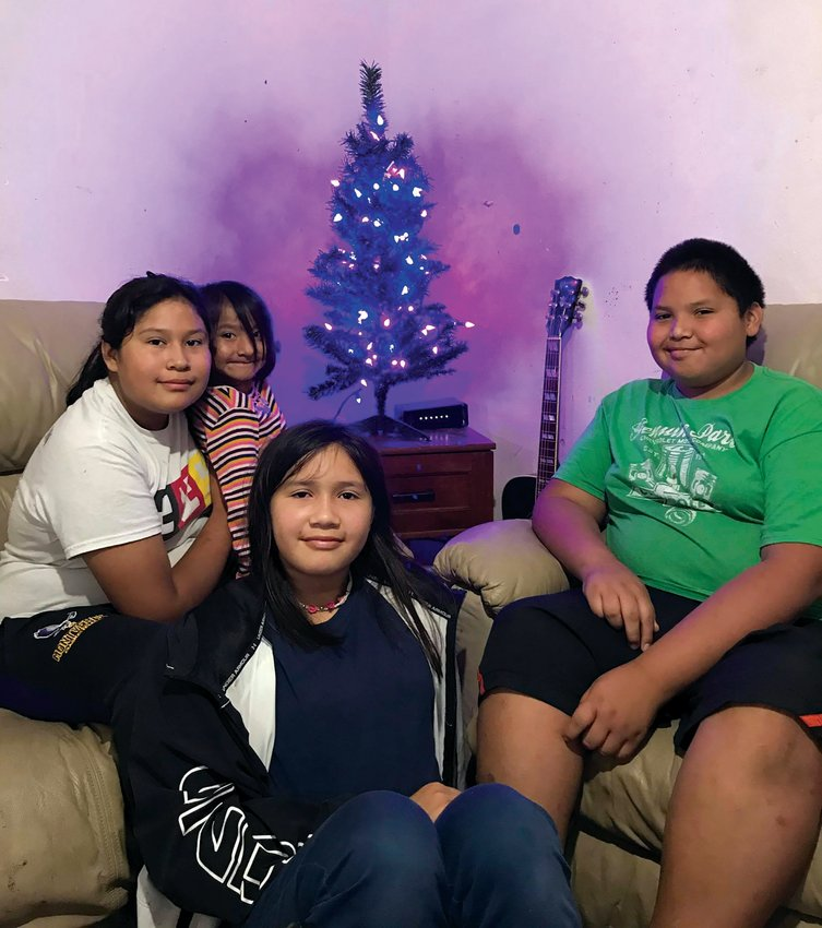 The Osceola children pose in front of their new Christmas tree.