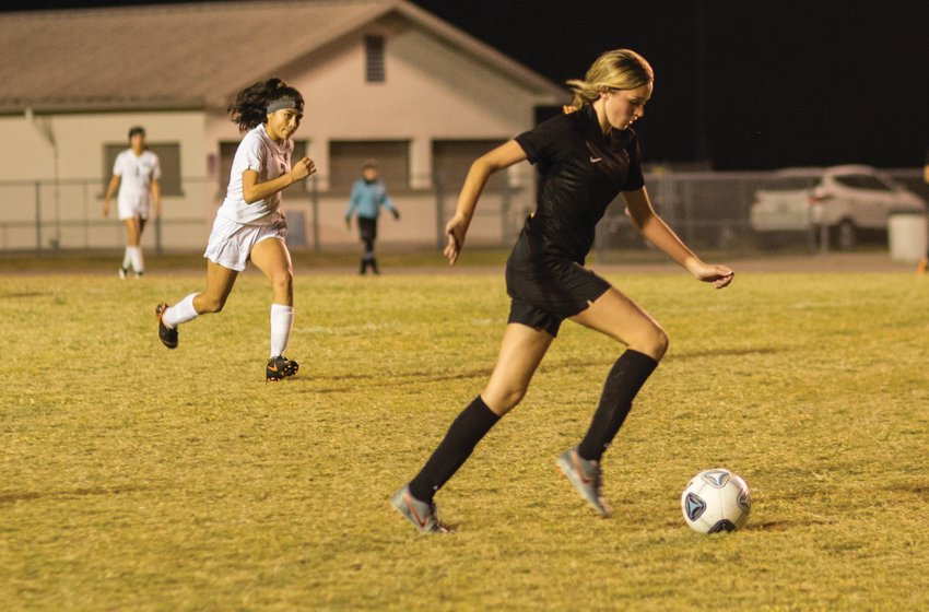 Makenna Smith drives the ball down field against the Lake Placid defense.