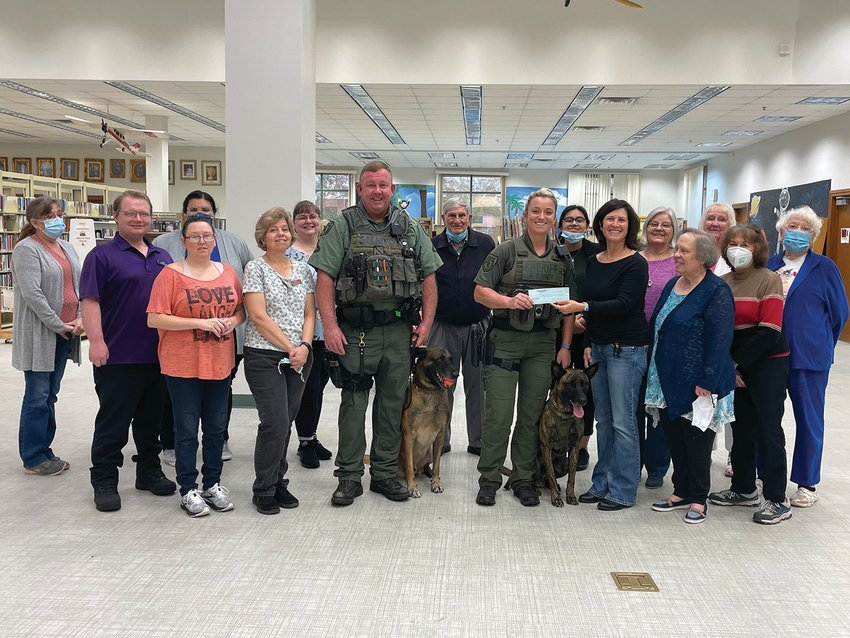 Okeechobee Friends of the Library present a donation of $500 to the OCSO K-9 program. Pictured are Okeechobee Conty library staff, OCSO Deputies Brian Cross with Magnum and Ashley Waskiewicz with Storm and the Friends of the Library.