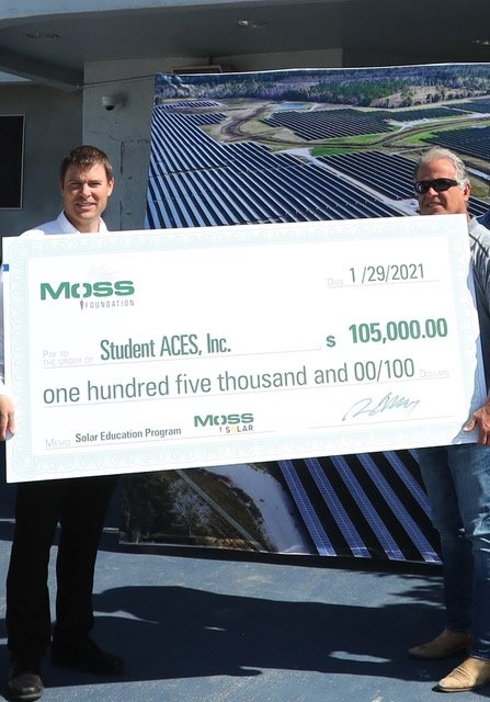 Mark Sochacki, Vice President/ Project Executive, Moss Construction, presents a $105,000 donation to Student ACES founder Buck Martinez at the organization's center in Belle Glade.