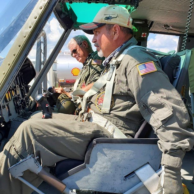 Todd Chambers flies with the Friends of Army Aviation in a UH-1 Huey at a Vietnam Veterans event.