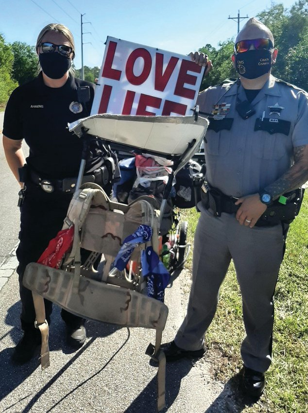 """Collier County Deputies, CSD Ahrens and Corporal Johnny Cisnero stopped to have their photo taken with the famous """"LOVE LIFE"""" sign that Steve Fugate wears above his head while he walks."""