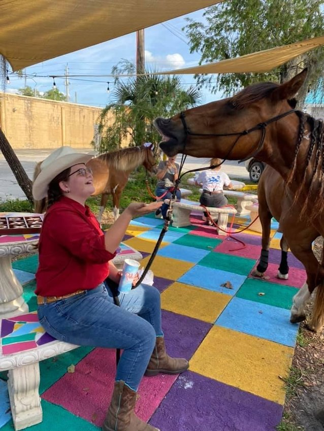 Local youth trainer, Izzy Rodriguez, and her mustang, Willow, visit Pelican's Snowballs in LaBelle as part of their training program.