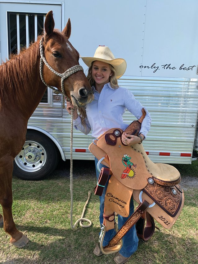 Brilee Cochran shows off the saddle she won as the State Cutting Champion.