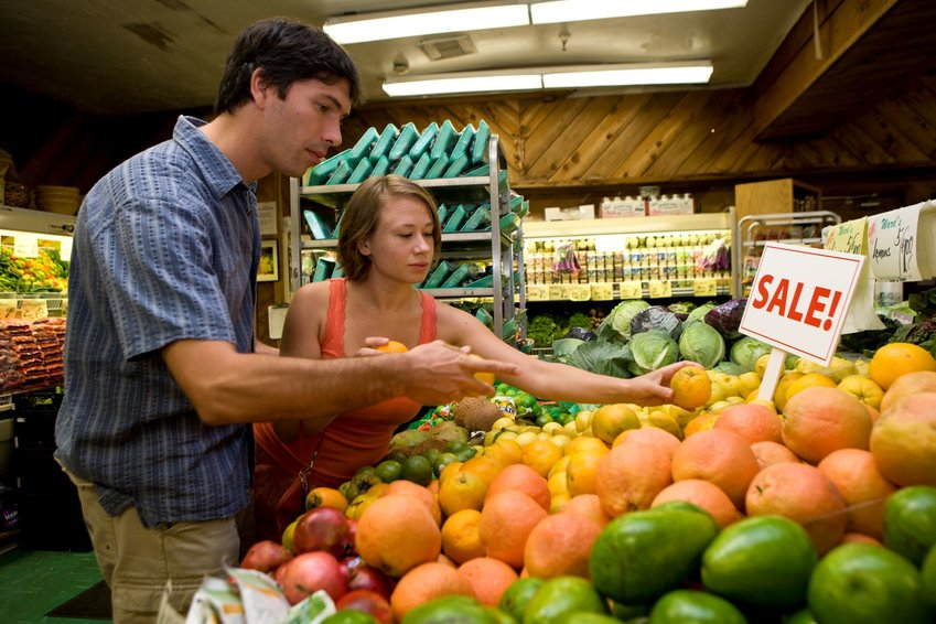 A couple (pre-COVID) picking out produce at a grocery store.