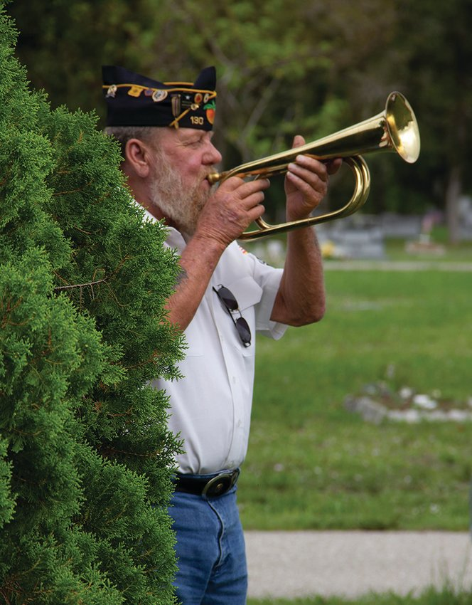 Commander of the American Legion Bill Davis, plays Taps at the Ft. Denaud Cemetery.