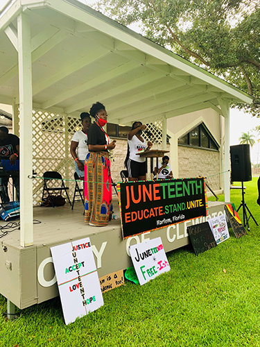 Speakers took the stage, adorned with signs, for the first-ever Hendry County Juneteenth Celebration in Clewiston's Civic Park.