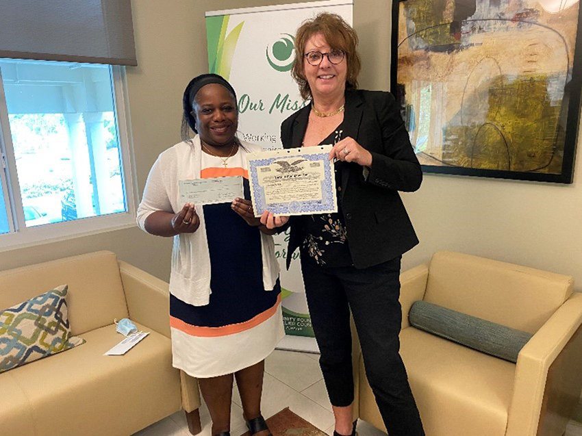 Left  - Marie Capita, the TOI Executive Director, receives a check from a Tamiami Angel Funds Board Member.