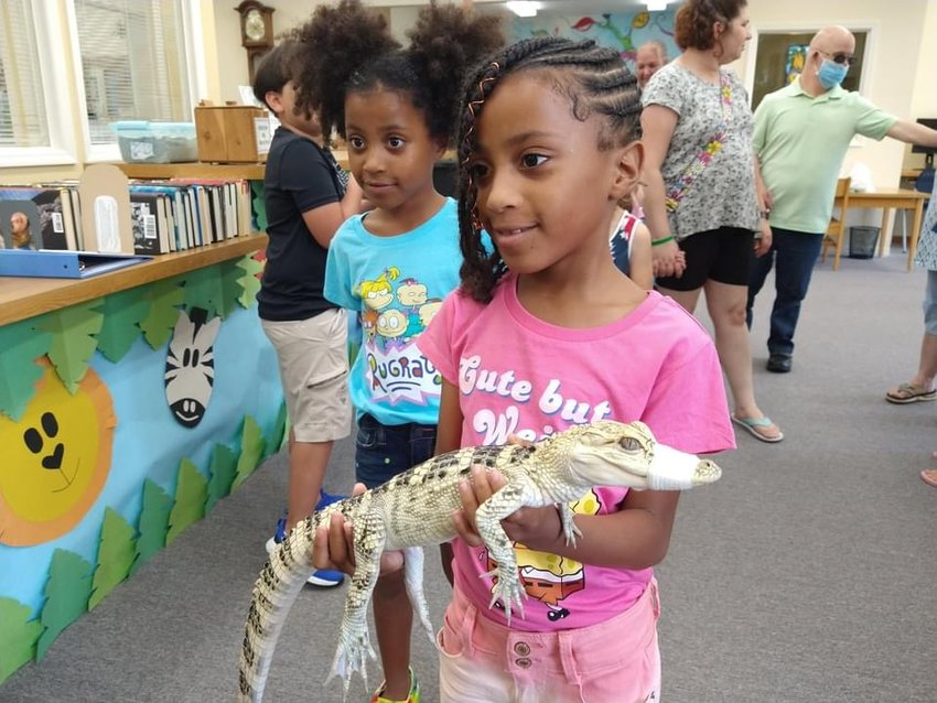 Children hold an alligator at the Barron Library's weekly Tales and Tails story time event.