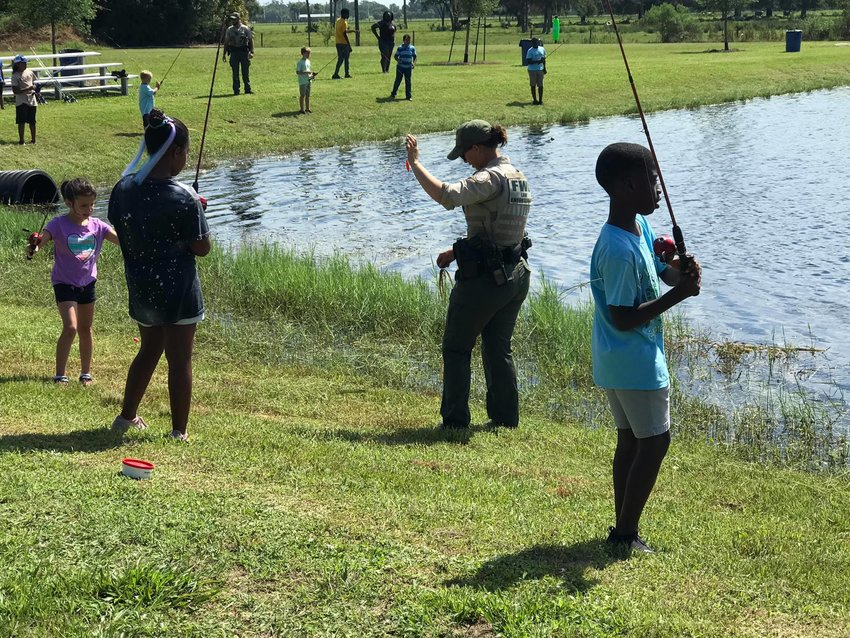 Local children enjoy a fishing trip while at day camp.