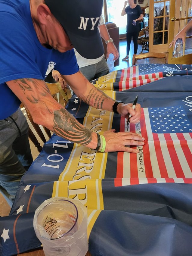 9/11 hero signs flag during the Healing Heroes Golf Tournament.