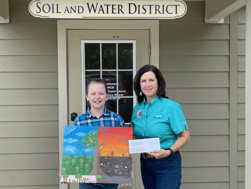 In the above photo, Program Specialist with the Okeechobee Soil & Water Conservation District Robbi Sumner presents Lillian Stead with her award check.