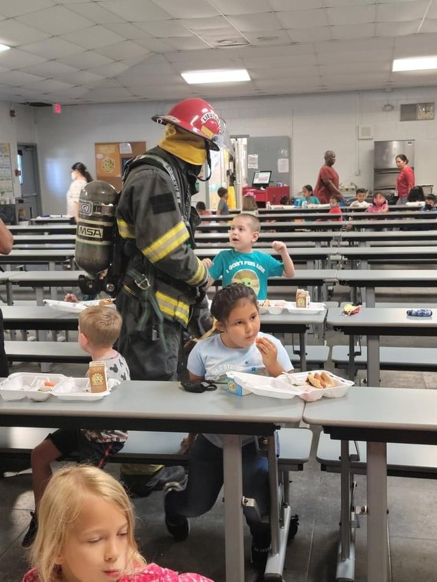 A LaBelle firefighter shows students their turnout gear.