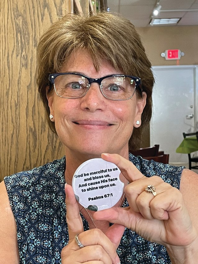"""""""It's not about me. It's about Him,"""" said Kelly Owens, holding up the car coaster she had designed as a token for her Prayer 67 group."""