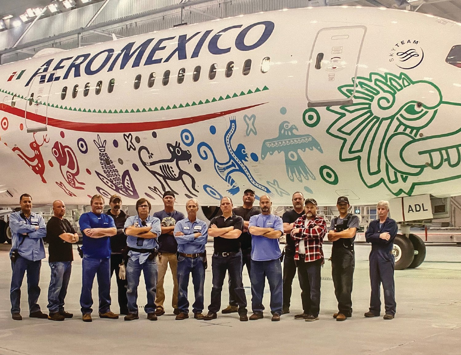 Gary Walker (eighth from left) with his Boeing teammates and an Aero Mexico 787 in the background inside the paint hangar at the Boeing plant in Everett, Wash.