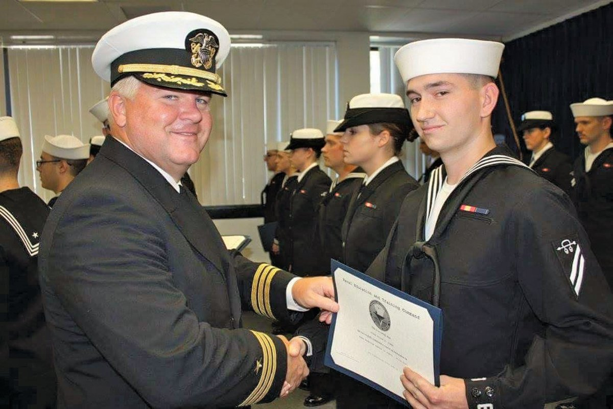 Dillon Jones graduates from sonar technician A school. The FASW Training Center executive officer hands him his certificate signifying he is now officially an STG (or Sonar Technician – Surface).