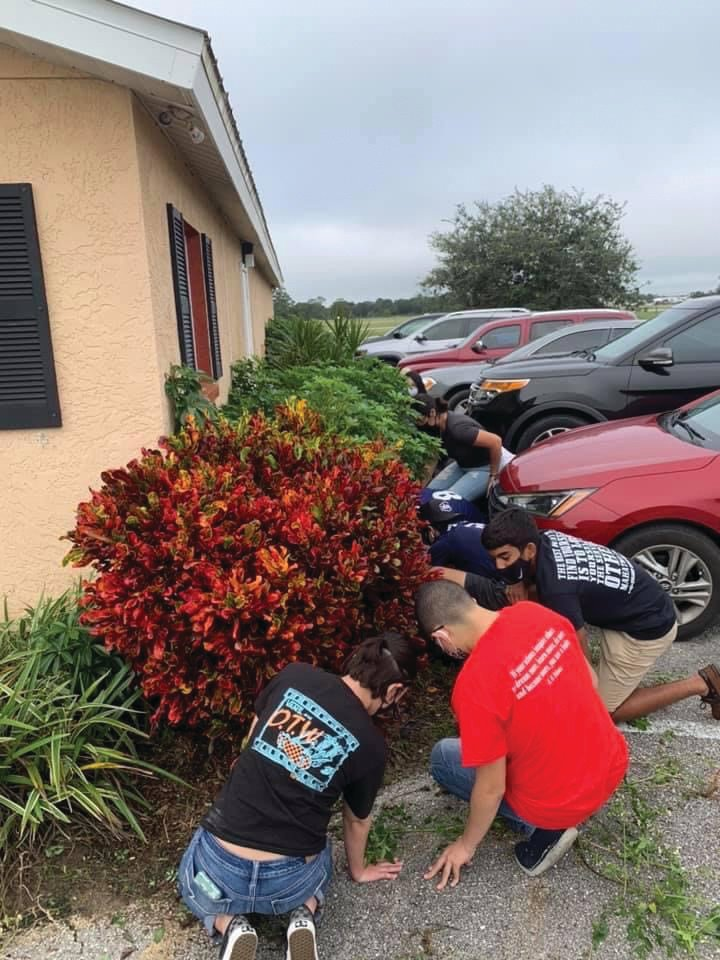 LHS National Honor Society Students work to help with landscaping and maintenance around the Caloosa Humane Society building.